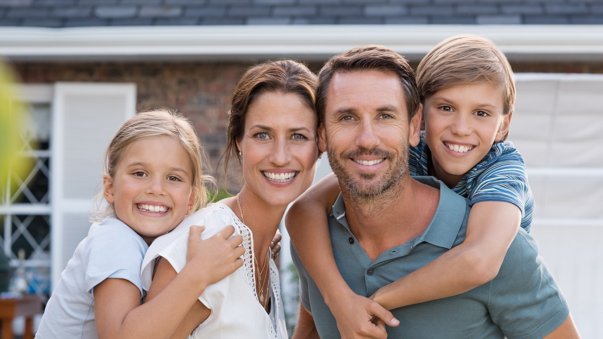 young-family-in-front-of-house